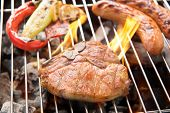 pic of grilled sausage  - Pork chop steak and vegetable with sausage on a flaming BBQ grill - JPG
