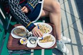 picture of smoking woman  - A young woman is eating cokcles and smoked fish outside on a sunny day - JPG