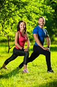 image of stretch  - Man and woman doing stretching exercises at summer park - JPG