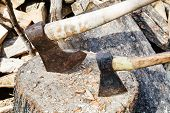foto of cleaving  - two axes in block for chopping firewood close up - JPG