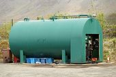 image of fuel pump  - A green fuel storage tank with a pump unit on concrete with waste bins underneath - JPG
