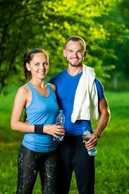 pic of cold drink  - Man and woman drinking water from bottle after fitness sport exercise - JPG