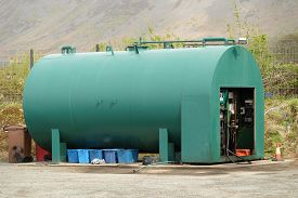 picture of fuel pump  - A green fuel storage tank with a pump unit on concrete with waste bins underneath - JPG