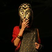 Woman Looks Through African Mask