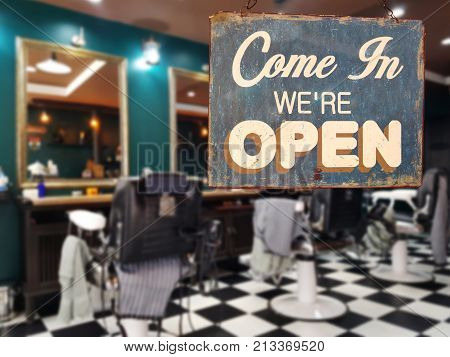 poster of a business vintage sign that says 'Come in We're Open' on barber and hair salon shop window. image of abstract blur barber and hair salon shop business without people for background usage
