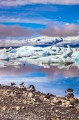 Sunrise illuminates the glacier Vatnajokull and water of Ice Lagoon Jokulsarlon. Several geese grazi poster