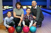 Family from four persons  of squatting in club for bowling and holds on to balls, focus on children