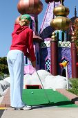 foto of miniature golf  - young woman playing miniature golf - JPG
