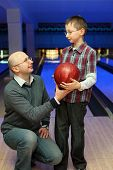 Father gives  son  red ball for bowling