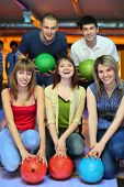 Three girlfriends squatting and behind stands two fellows  and everybody holds ball for bowling, foc