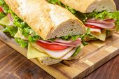 Baguette sandwich cut in half with ham,  turkey breast, cheese, lettuce and tomatoes on a cutting bo poster