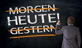 Businessman Writes In German Today, Yesterday, Tomorrow On Blackboard Concept poster