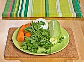 Carrots, Parsley, Onion, Vegetable Marrow On A Green Plate