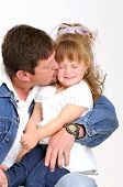 young father dressed in jeans and toddler girl dressed in white hugging and kissing