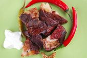 grilled meat chunks on green plate over white