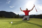 Professional young male golf player on knees and arms raised with putter in hand on golf green being