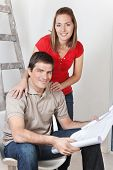 Portrait of young happy couple together with blueprints