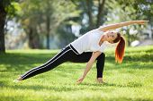 Yoga outdoor. Happy woman doing yoga exercises, stretching in the park. Yoga meditation in nature. C poster