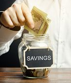 A Man Puts Dollars In A Glass Jar With The Word Savings. The Concept Of Managing A Family Budget. Di poster