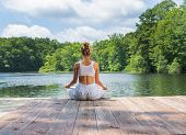 Attractive Woman Is Practicing Yoga And Meditation Sitting In Lotus Pose Near Lake. Young Woman Is M poster