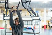 Front view of young fit Caucasian man exercising with shoulder machine in fitness studio. Bright mod poster