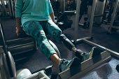 Low section of disabled active senior Caucasian woman with leg amputee exercising with leg press mac poster