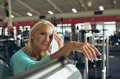 Front view of tired active senior Caucasian woman wiping sweat towel in fitness studio. Strong activ poster