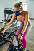 Front view of beautiful young Caucasian female athlete with oxygen mask exercising with exercise bik poster