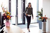Businesswoman Arriving For Work At Office Walking Through Door poster