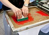 stock photo of labourer  - manual screen printing - hand printing t-shirts