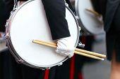 Mit einer Hand und Drumsticks auf Parade Trommel