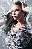 A portrait of a mysterious lady in a silver dress with flowers posing indoor. Fairy tale, fashion. poster