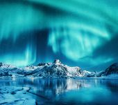 Aurora Borealis Above Snowy Mountains, Frozen Sea Coast And Reflection In Water In Lofoten Islands,  poster