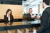 Smiling Executive Giving Access Key To Entrepreneur Standing While Colleague Talking On Phone At Cou poster