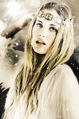 stock photo of headband  - Artistically toned image in cool tones of a beautiful blonde woman in white with a jewelled headband standing under falling snowflakes during winter in a enchanting snow princess concept - JPG