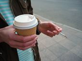 Person Hand Holds A Paper Disposable Cup Of Coffee And A Steaming Cigarette. Bad Habits, Health Prob poster