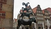 Bronze Statue Of The Town Musicians Of Bremen In Old City Centre, Beautiful Houses On The Background poster