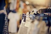 Clothes On Hangers In Shop For Sale. Blur Background. Fashionable Clothes In A Boutique. Various Clo poster