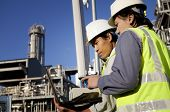 picture of workplace safety  - two engineer power and energy discussion on location site using laptop - JPG