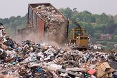stock photo of truck  - A bulldozer moving garbage on a landfill waste site as a garbage truck dumps more - JPG