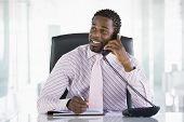 Empresario sentado en la oficina con agenda abierta en el teléfono