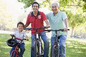 Grootvader zoon en kleinzoon fiets rijden.