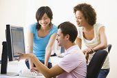 Drie mensen In computerlokaal wijzend op de Monitor en glimlachen