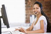 Businesswoman In Office Wearing Headset And Typing On Computer Smiling