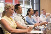 Cinco empresarios en la sala de juntas mesa sonriendo