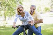 pic of portrait middle-aged man  - Man pushing woman on a bike in a park - JPG