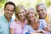 stock photo of middle-age  - Two Couples sat in a park smiling - JPG