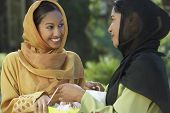 picture of dupatta  - Two happy Asian women looking at each other while holding shopping bags - JPG