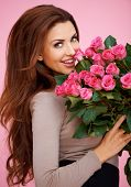 stock photo of fragrance  - Laughing romantic sexy woman with long brunette hair holding a large bouquet of pink roses for her anniversary or Valentines - JPG