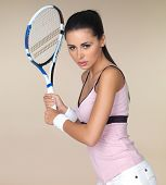 Attractive woman in sportswear playing tennis holding her racquet in both hands ready to play a backhand shot isolated on beige